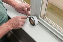 A worker installs insulation in window.